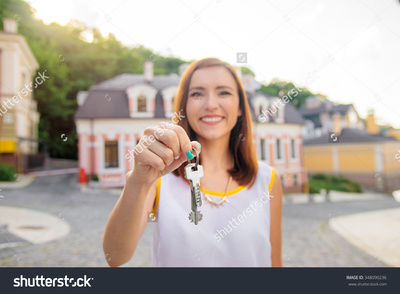 Stock photo real estate happy broker attractive young woman holding keys while standing outdoor against new 348090236 %281%29
